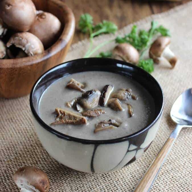 An Asian designed bowl is filled with creamy mushroom soup and garnished with wild mushroom slices.