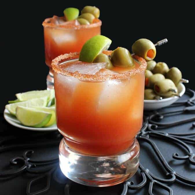 Michelada Mexican Bloody Mary with one tomato rich drink sitting in front of another. Garnished with olives and lime and rimmed with chili seasoning and salt.