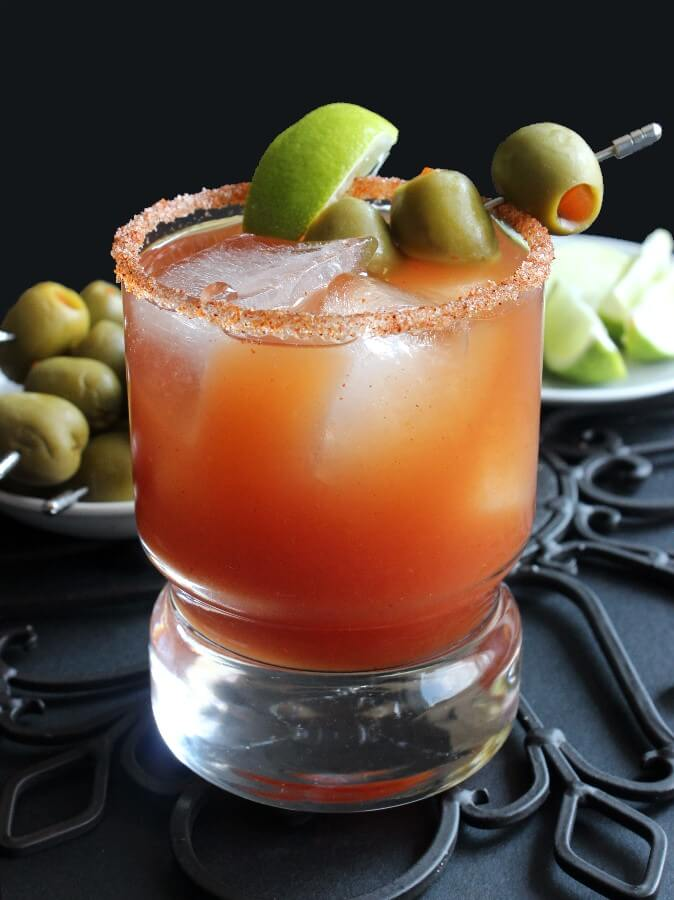 Michelada Mexican Bloody Mary with one tomato rich drink front and center. Garnished with olives and lime.