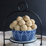 Overflowing blue bowl of beautiful ivory peanut butter balls.