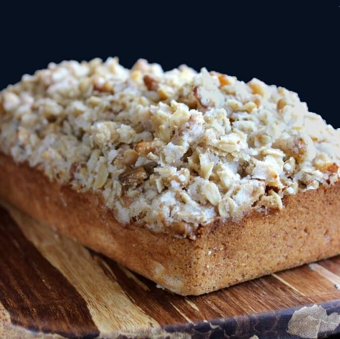 Streusel topping is baked on top of a banana bread loa.