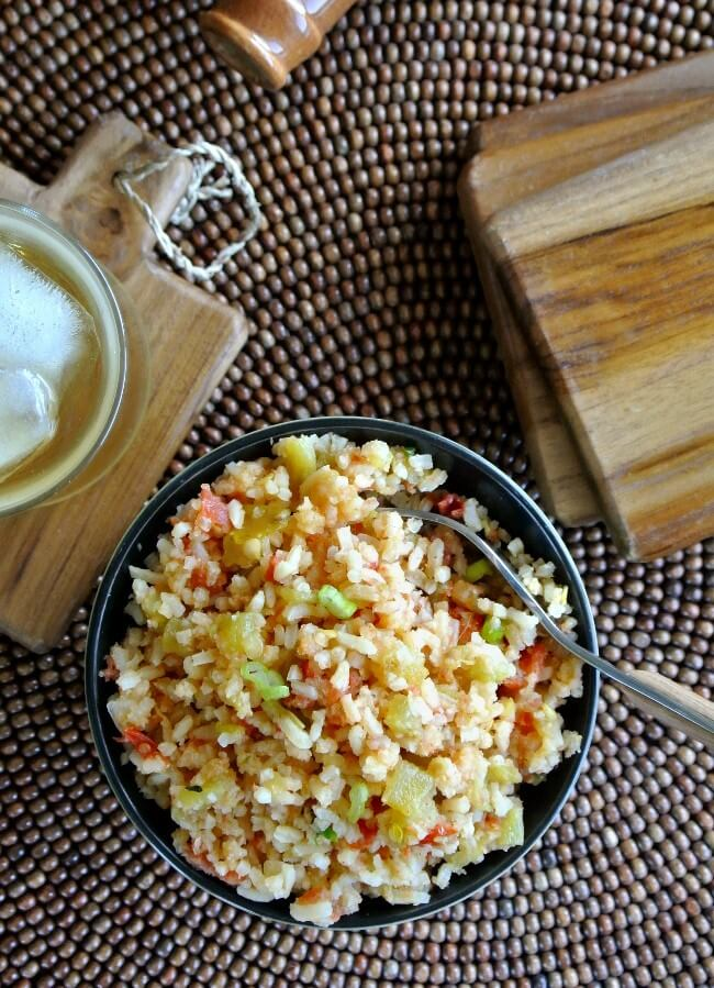 Overhead photo of a protein rice side dish on a brown wood mat with iced tea on the side.