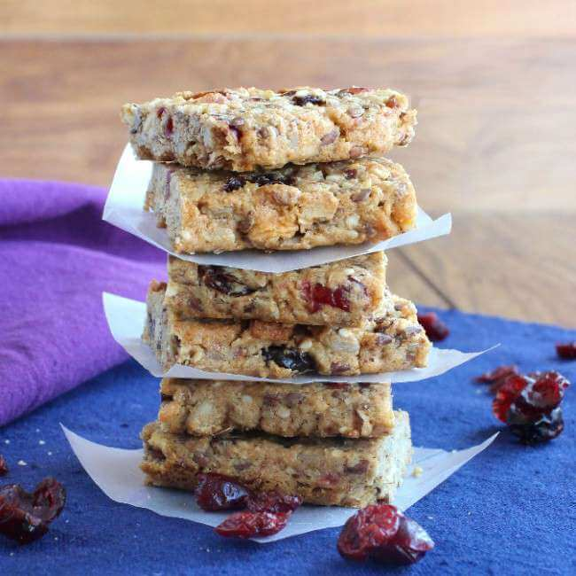 Cranberry Date Breakfast Bars are stacked 6 high and separated by parchment squares.
