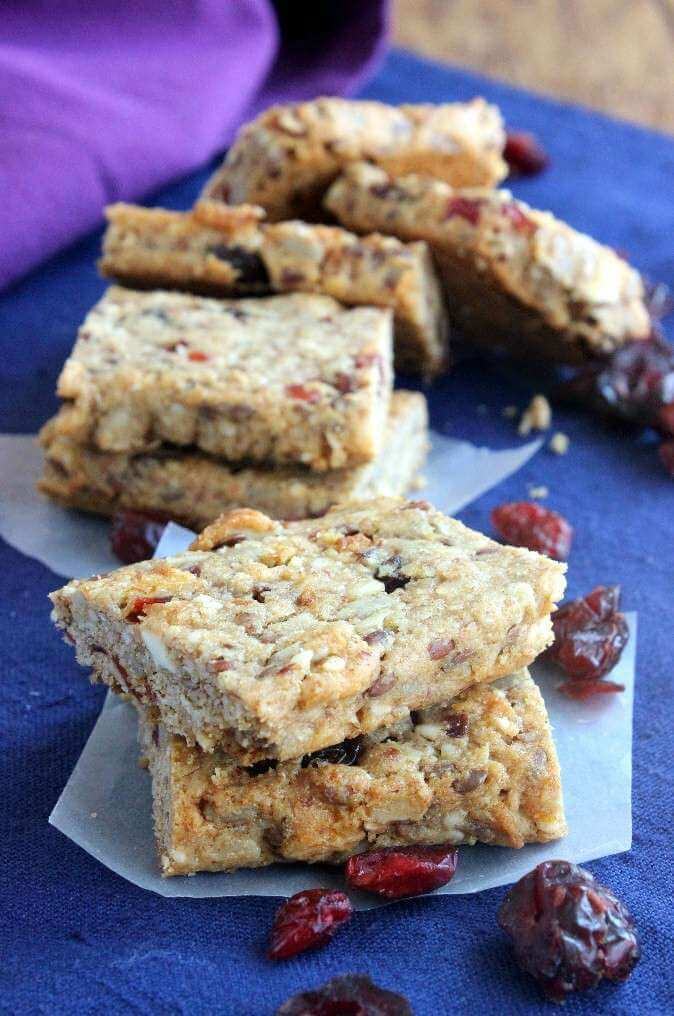 Healthy breakfast bars are laying on a blue background showing fruit and nuts inside bars.
