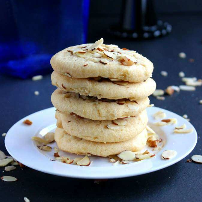 Chinese Almond Butter Cookies are in a stack of five and are sitting on a white plate with scattered slivered almonds.