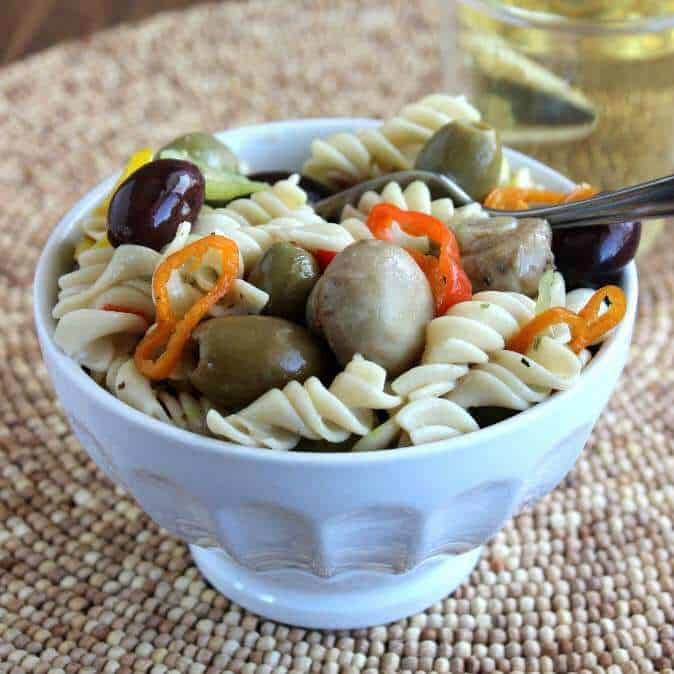 Quick Italian Pasta Salad perfectly centered and overflowing in a white bowl.
