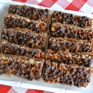 Chewy chocolate chip bars are lined up in two rows on a white square plate.