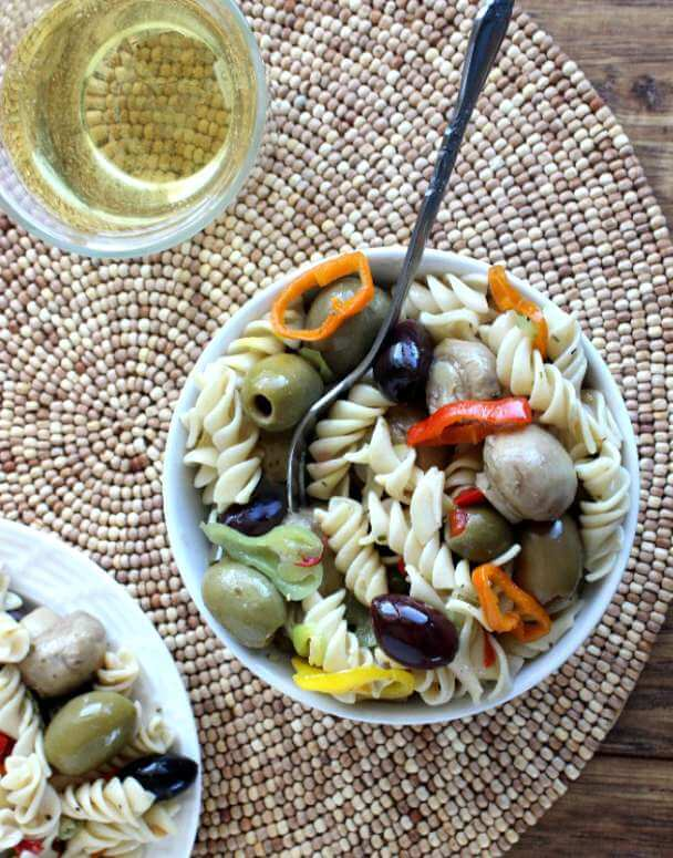 Quick Italian Pasta Salad as an overhead photo with a fork sticking off and angled t the side. White wine is sitting to the left.