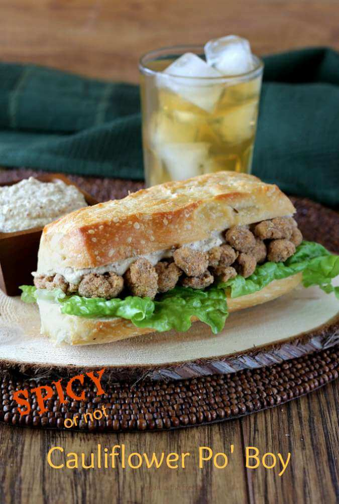 Cauliflower Po' Boy is a big hoagie sandwich with golden breaded balls of cauliflower peeking out with lettuce and creamy condiments.