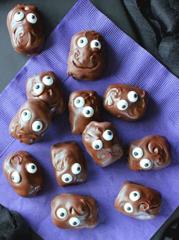 Copycat Almond Joy Candy Bars are shaped like fat chocolate heads with big candy eyes and swirly chocolate hair.