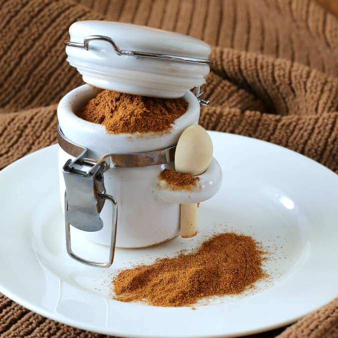 Homemade Pumpkin Pie Spice Blend is spilling out of a mini white crock and has made a small pile on the white plate below. A contrasting rust colored cloth is below all.