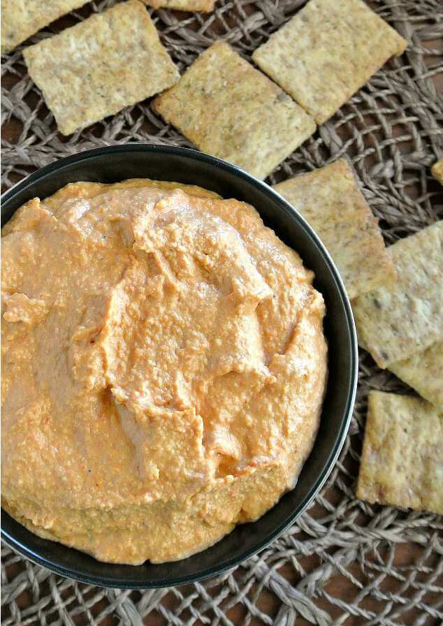 Roasted Red Bell Pepper Hummus is an overhead shot of rosy red hummus filling a bowl with little square wheat thins sprinkled around.
