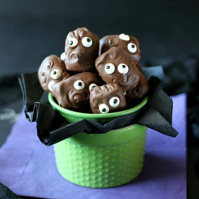 Chocolate cover candy bars in a green bowl with a black tissue poking out below. Added candy eyes for fun!.