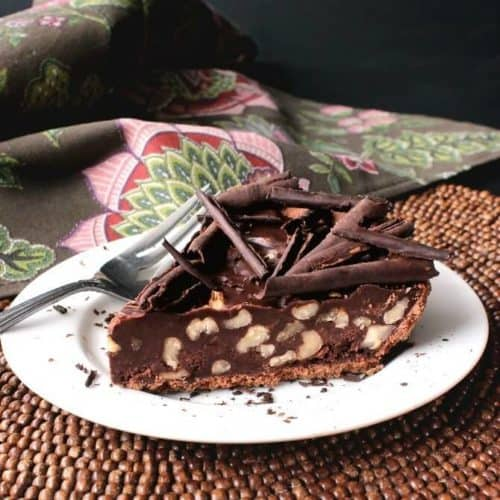 A sideways view of chocolate pie in a chocolate crust with walnuts and shaved chocolate on top.