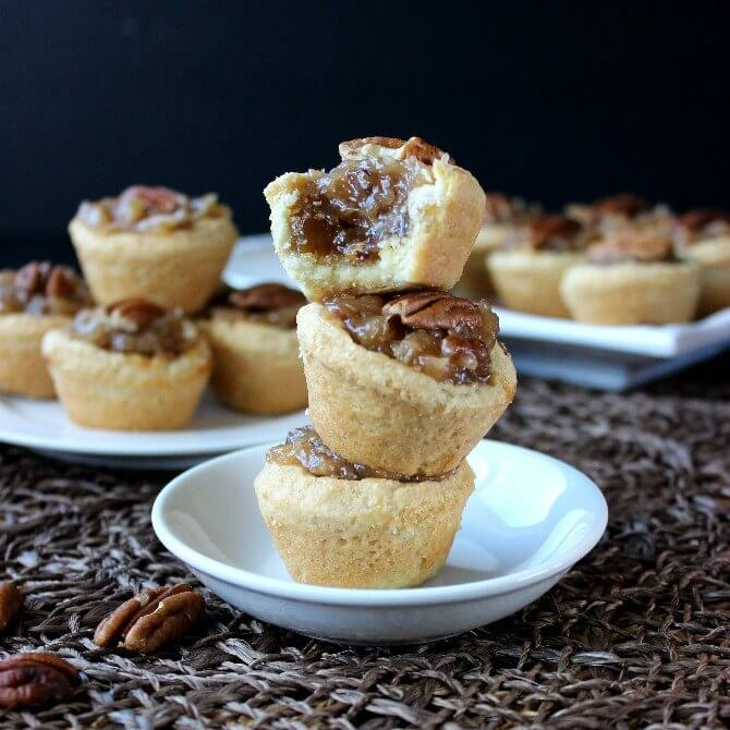 Mini Pecan Pie Tarts are over the top decadent and fit right in at any family gathering or through an elegant party.
