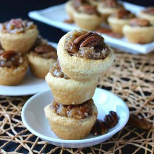 Mini Pecan Pie Tarts stacked three high with more mini behind.