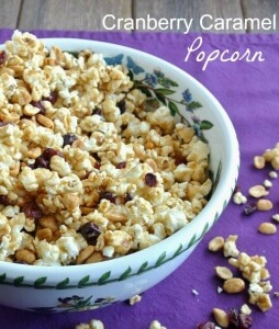 Cranberry Caramel Popcorn is golden in color and spilling out of a ivy designed bowl onto a purple cloth.