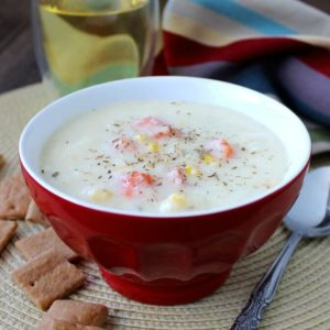 Creamy white Cauliflower Soup is in a red bowl with carrots and corn showing on the surface.