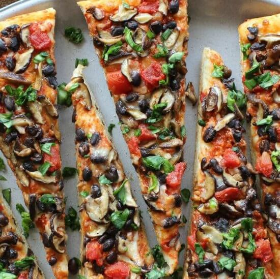 Mexican Style Baby Shiitake Mushroom Pizza with a close up of pizza slices showing lots of veggies on a red sauce. Veggies such as shitake mushrooms, black beans, tomatoes and parsley.