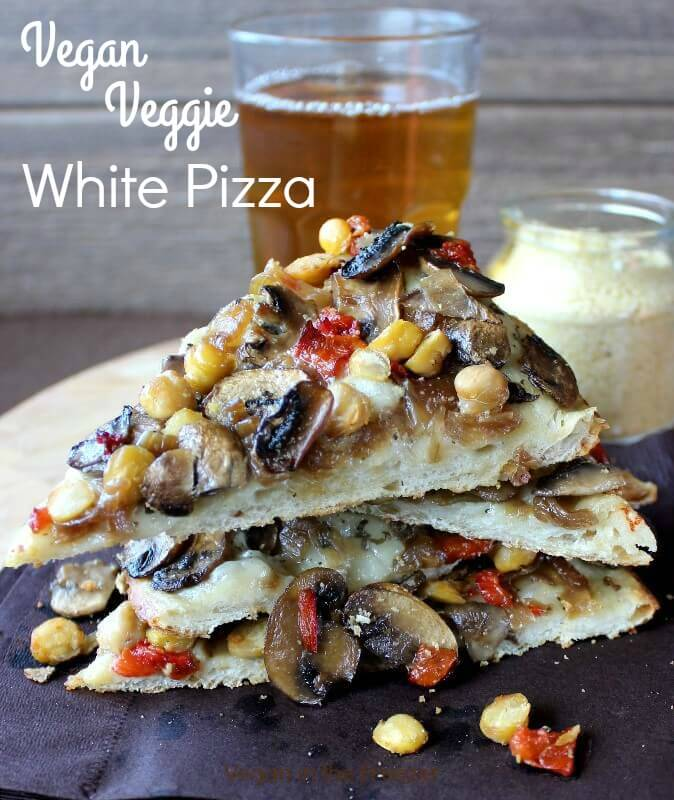 Vegan Veggie White Pizza sliced and stacked on top of each other with a frosty beer standing behind.