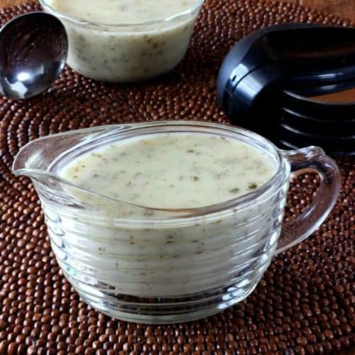 Vegan White Pizza Sauce is in a clear glass ridged creamer with more sauce and a scoop behind.