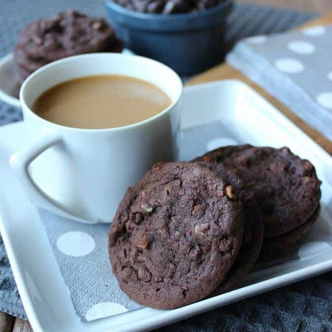 Irish Cream Chocolate Cookies are on a square white plate with a silver polka dot napkin underneath with a cup of coffee on the side.