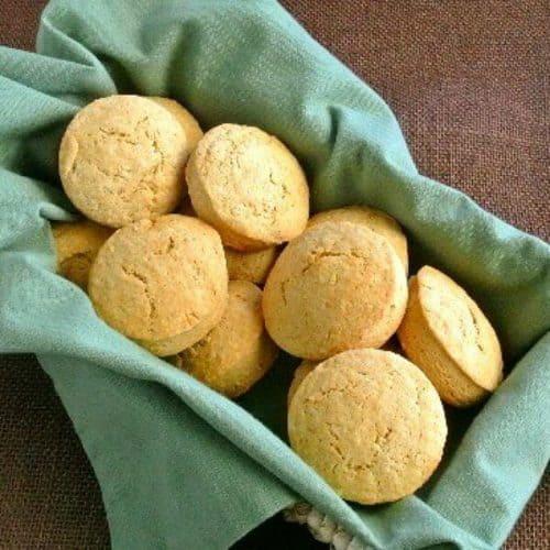 A basketful of 12 round scones in a green cloth napkin.