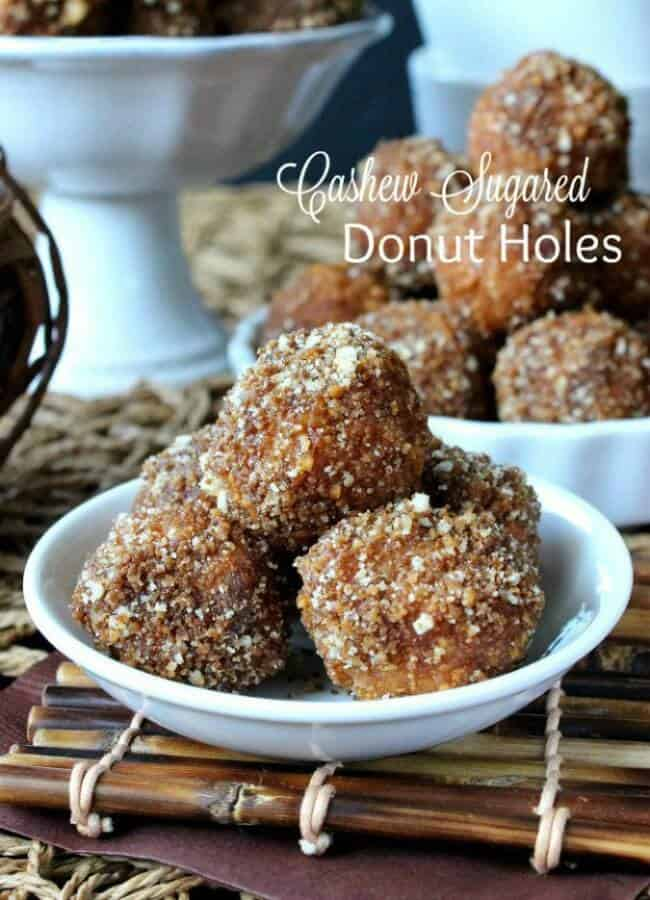 Cashew Sugared Donut Holes are five deep in a mini white bowl. Crumbly cashew sugar is all over these little bites and the are also sitting on a bamboo mat.