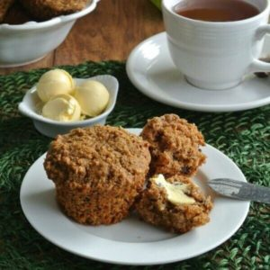 Healthy Morning Muffins are split open and buttered on a white plate and green mat.