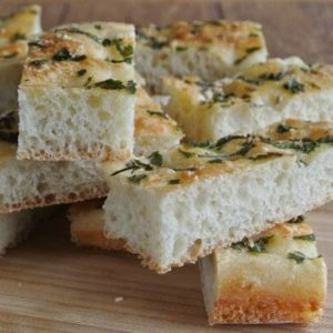Herbed Focaccia is cropped for this photo and is a closeup of long fat and narrow slices that would be perfect for biting or dunking.