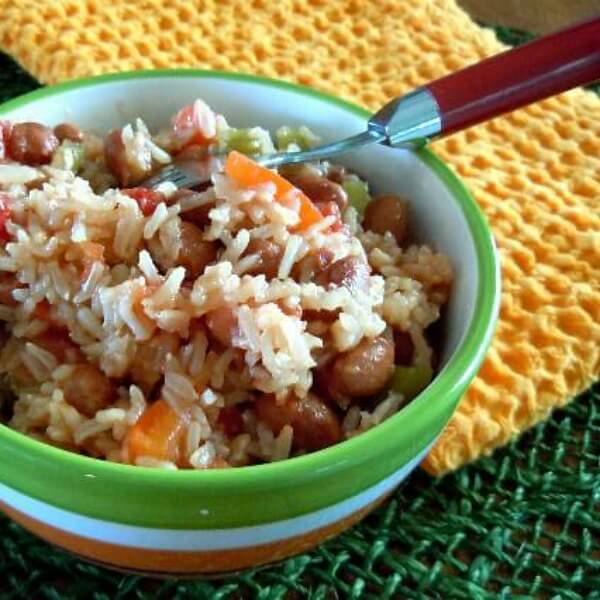 Spanish Rice mixed with pinto beans is in a bright green and white bowl and set against an orange cloth to bring out the orange in the carrots.