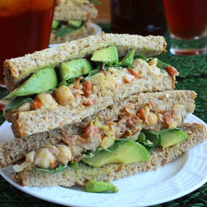 Loaded Chickpea Salad Sandwich is sliced in half and the halves are stacked on top of each other so you can see all of the colorful ingredients.