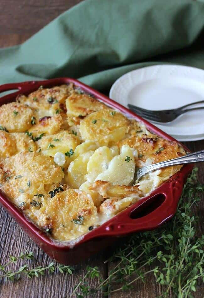 Dairy Free Herbed Scalloped Potatoes baked to a golden color and served in a red casserole. A large serving spoon is scooping out the first serving.