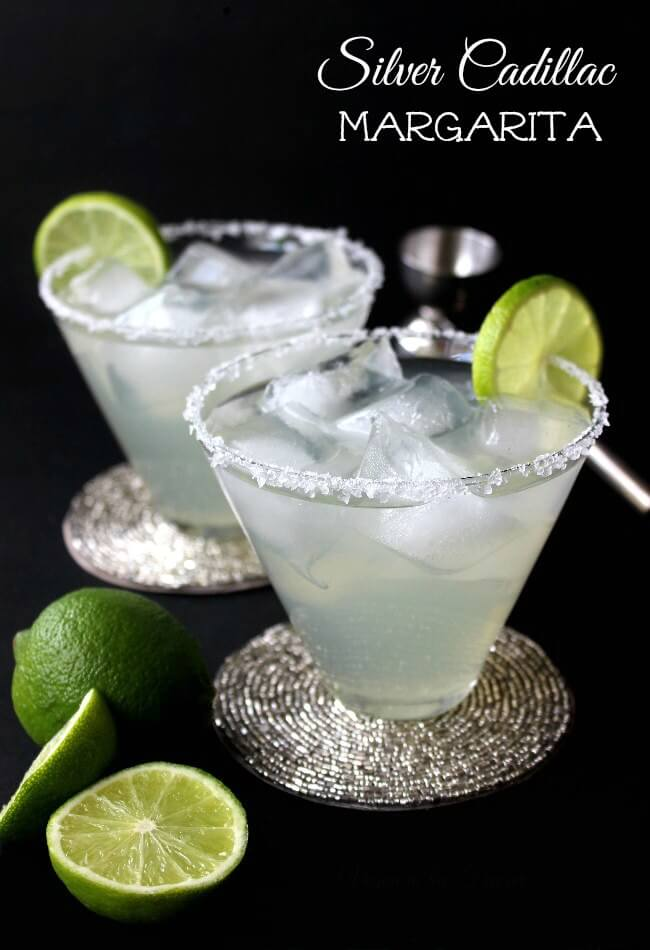Silver Cadillac Margarita is silvery in hue and two flared glasses are filled over ice cubes. Lime slices are slid onto the salt covered rims.