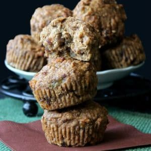 Three Muffins are stacked on top of each other with one broken open on the top with brown and turquoise background.