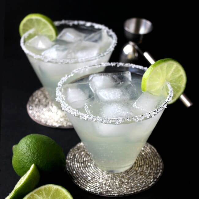 Silver Cadillac Margarita in a flared glass with lime on the edge.