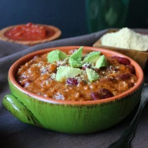 Two Bean Camp Chili is front and center in a green bowl siting on a brown cloth napkin. Rich red beans are topped with triangle cut avocado.