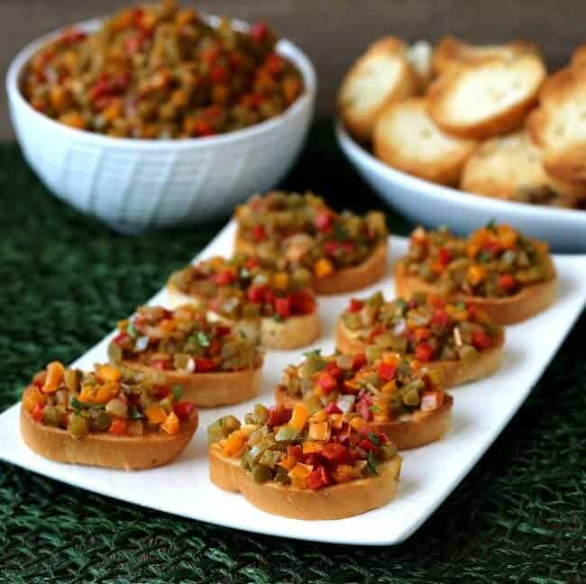 A tilted rectangle platte has loaded crostini lined up wit more bell pepper bruschetta crostini.