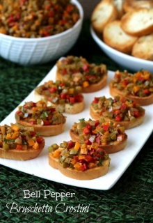 looking down on two rows of little toasts piled high with easy bruschetta recipe.