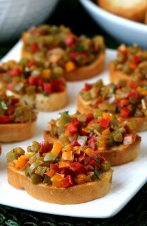 Close up of angled mini toasts covered with vegan bell pepper crostini.