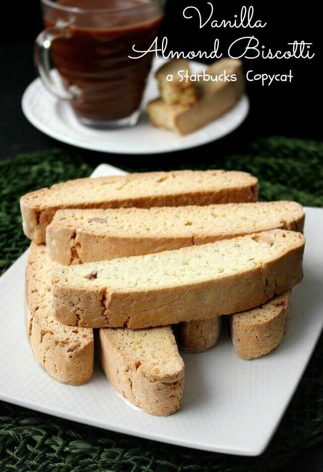 Vanilla Almond Biscotti {Starbucks Copycat} are randomly stacked with seven biscotti cookies with a cup of chocolate coffee behind for dunking.