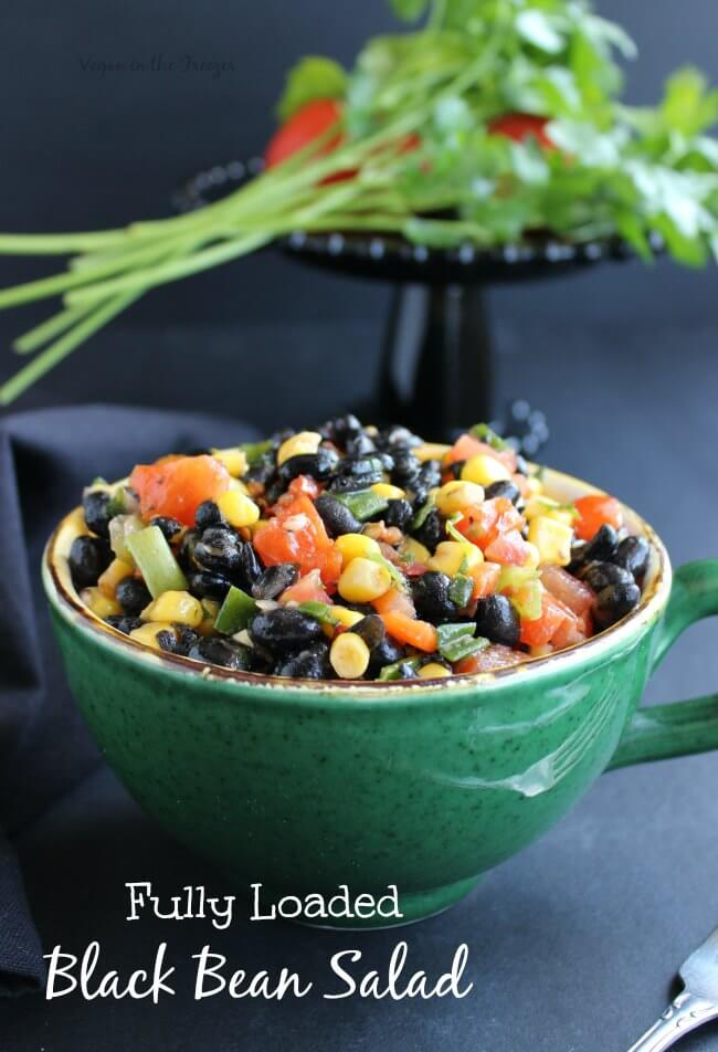 A green bowl filled with veggies and beans and tossed for a cool salad.