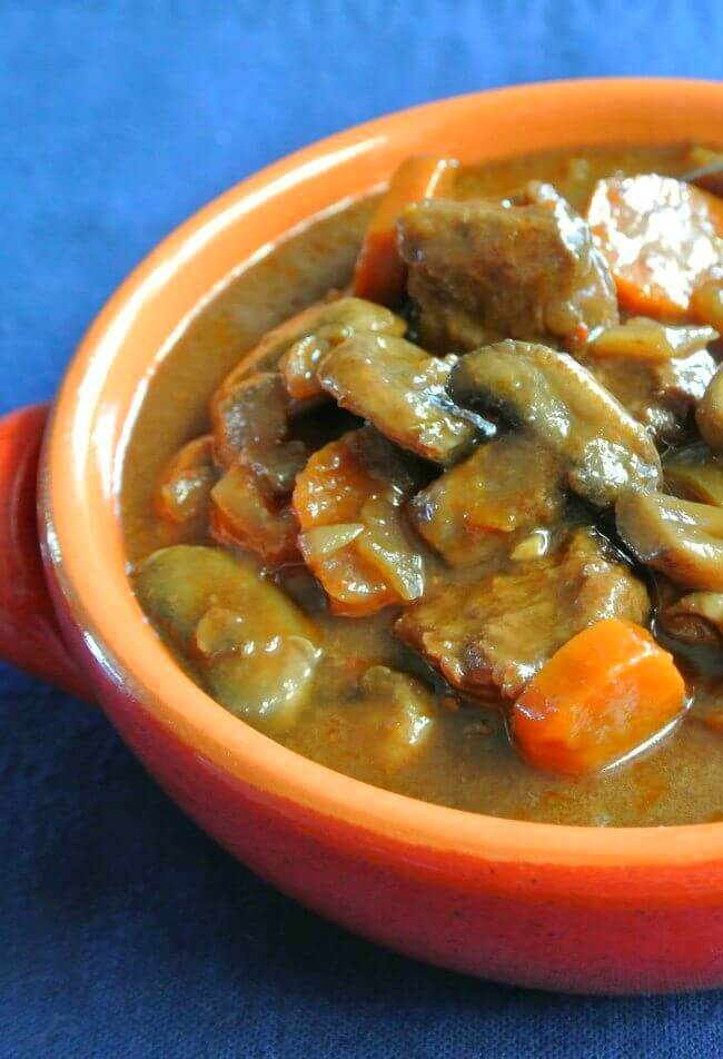 Angles and cropped photo showing a bowlful of a stew with carrots, mushrooms and plant based beef cubes.