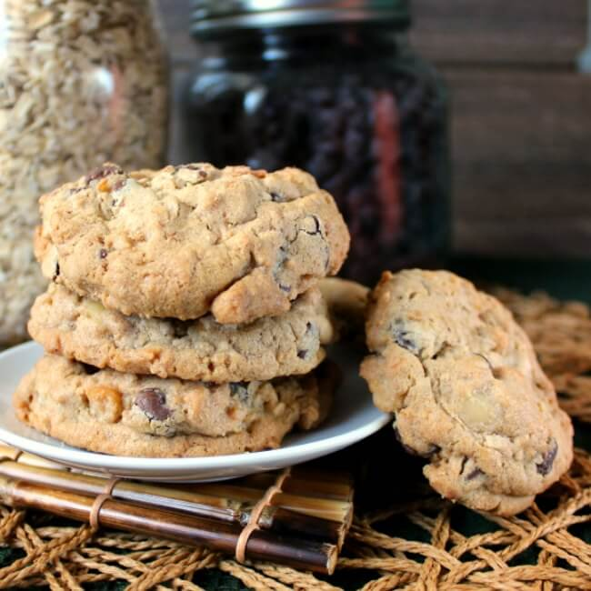 Nut Free Oatmeal Chocolate Chip Cookies are stacked three high on a small white plate and a woven mat. One cookie is set on the side at an angle.