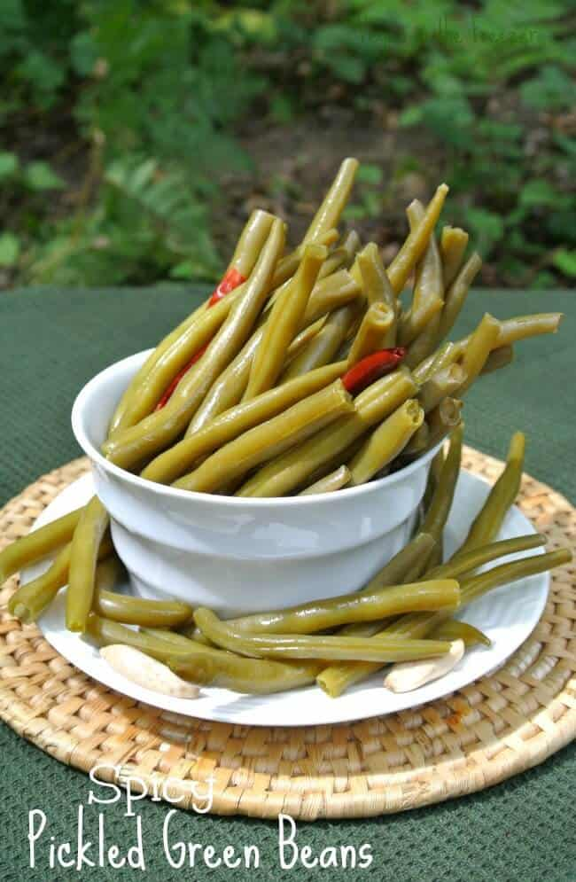 Spicy Pickled Green Beans are piled at an angle just ready for the picking out of a white bowl with red peppers peaking though.