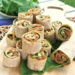 Sun-Dried Tomato Pesto Tortilla Rollups are sliced and stacked on a wooden cutting board and placed on the picnic table for everyone to enjoy.