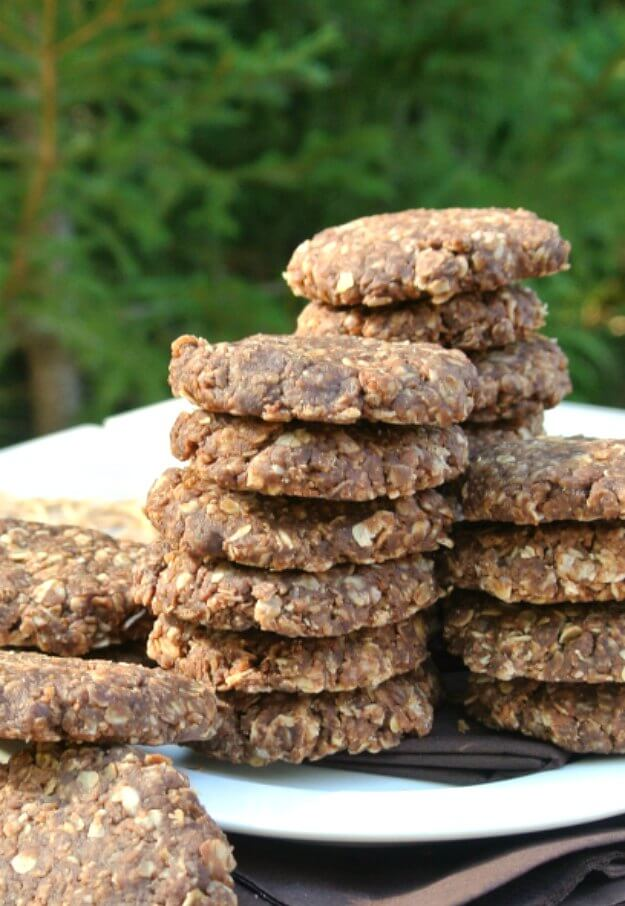 No Bake Chocolate Peanut Butter Cookies have a close-up and are stacked willy nilly on a white plate against a green background.