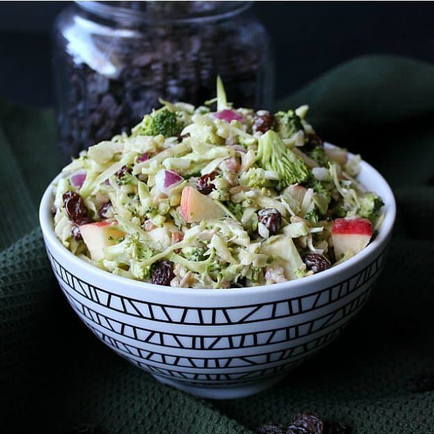 Vegan Apple Broccoli Salad is vividly colored in a zigzag patterned black and white bowl. Finely chopped vegetables and fruit fill the bowl. All against a black backdrop.