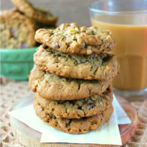 Dairy-Free Oatmeal Cranberry Cookies stacked 5 high on two golden napkins with an iced coffee on the side with a bowl of more cookies.
