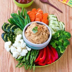 White bean dip is in a white bowl and is also surrounded of groups of sliced fresh veggies. All are on a round plate.